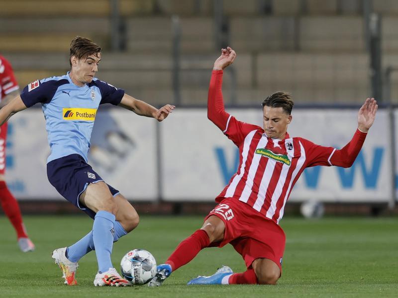 Der Freiburger Robin Koch (r) grätscht gegen Florian Neuhaus. Foto: Ronald Wittek/epa/Pool/dpa
