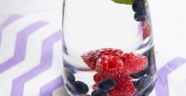 Bei Hitze ist mit Beeren und Minze versetztes Wasser besonders erfrischend: Aus Hygienegründen sollten Obst und Kräuter aber regelmäßig ausgewechselt werden. Foto: Catherine Waibel/dpa-tmn