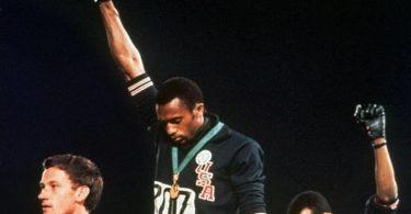 Die US-Athleten Tommie Smith (M) und John Carlos (r) streckten während Olympia 1968 die Fäuste, um gegen Rassismus zu protestieren. Foto: Anonymous/AP/dpa