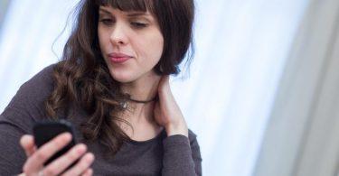 Immer mit gesenktem Kopf auf das Smartphone starren, kann zu Nackenschmerzen führen. Besser ist, nur den Blick zu senken. Foto: Christin Klose/dpa-tmn