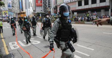 Die Polizei richtet eine Absperrung ein. Foto: Kin Cheung/AP/dpa