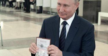 Wladimir Putin,Präsident von Russland, zeigt einer Mitarbeiterin der Wahlkommission seinen Pass in einem Wahllokal. Foto: Alexei Druzhinin/Pool Sputnik Kremlin/AP/dpa