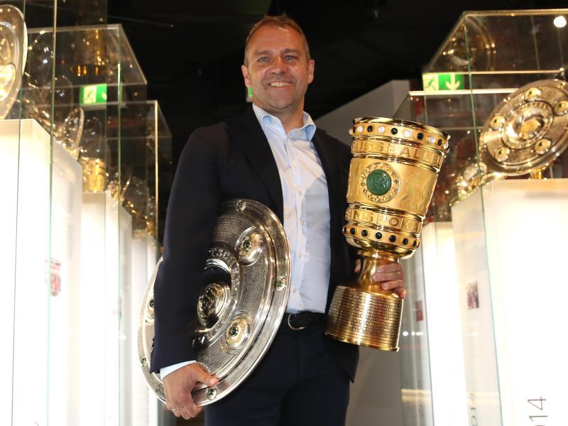 Coach Hansi Flick übergibt die Meisterschale und den Pokal an das Museum des FC Bayern München. Foto: Alexander Hassenstein/Getty Images Europe/FCB/dpa