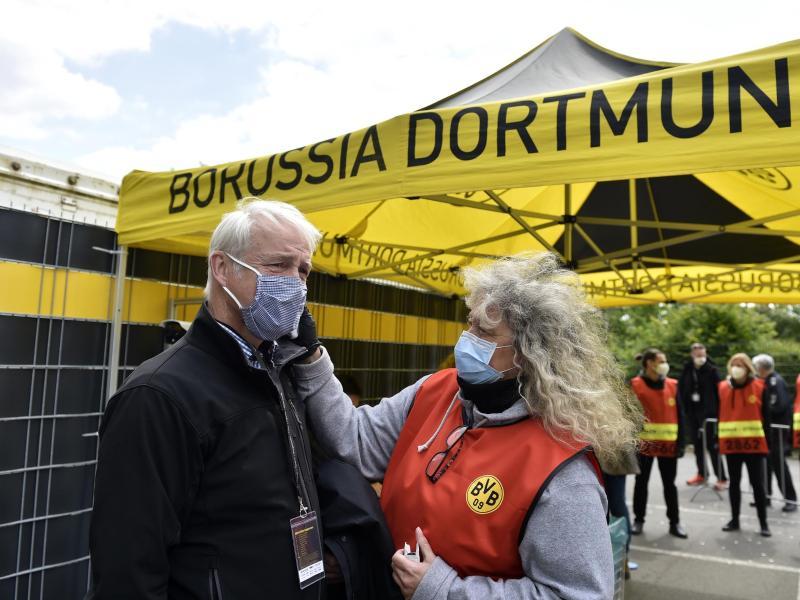 Beim Mitglied einer TV-Crew wird vor dem Einlass ins Stadion die Temperatur gemessen. Foto: Martin Meissner/AP-Pool/dpa