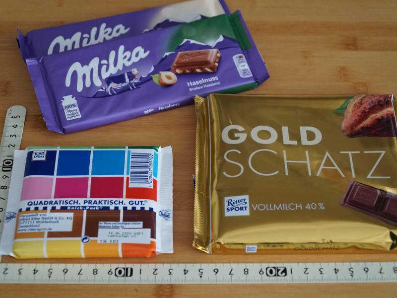 Schokoladentafeln der Marken Ritter Sport und Milka liegen neben einem Maßstab auf einem Tisch. Foto: Alexander Blum/dpa