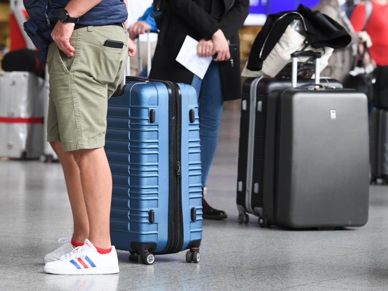 Flugreisende stehen in Terminal 1 des Frankfurter Flughafens am Check-in-Schalter an. Reiserückkehrer aus Risikogebieten sollen sich an Flughäfen verpflichtend auf das Coronavirus testen lassen. Foto: Arne Dedert/dpa