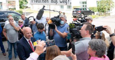 Andreas Kalbitz im Gespräch mit Journalisten - im Hintergrund haben sich Unterstützer versammelt. Foto: Sebastian Gollnow/dpa