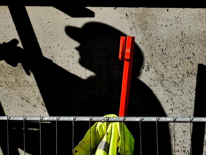 Ein Arbeiter ist auf einer Baustelle beschäftigt und wirft dabei einen dunklen Schatten. Die Wirtschaftsleistung in Deutschland ist im zweiten Quartal in Folge der Corona-Krise erheblich eingebrochen. Foto: Ralf Hirschberger/dpa-Zentralbild/dpa