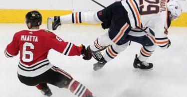 Edmontons Leon Draisaitl (r) wird durch Olli Maatta von den Chicago Blackhawks zu Fall gebracht. Foto: Jason Franson/The Canadian Press/AP/dpa
