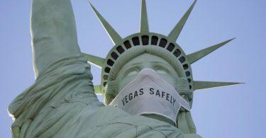 Eine riesige Maske ziert das Gesicht der Freiheitsstatue-Nachbildung in Las Vegas. Foto: John Locher/AP/dpa
