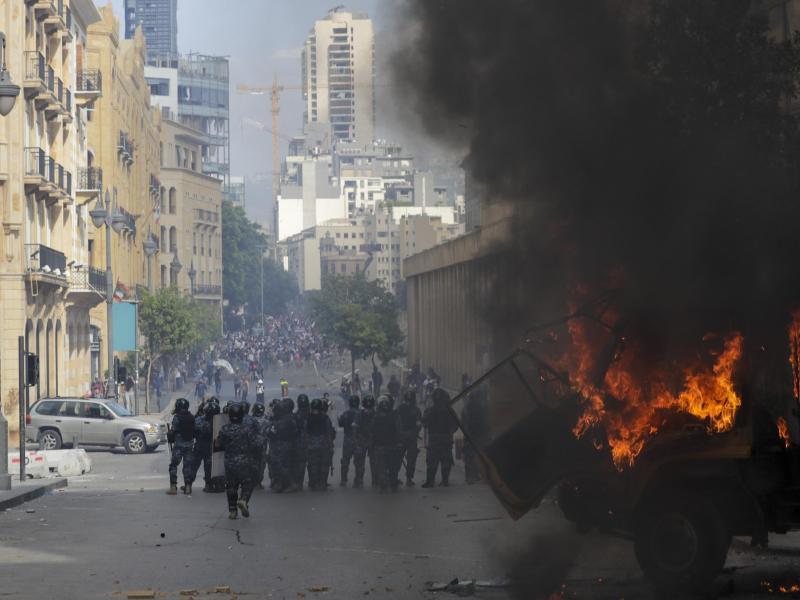 Einsatzkräfte stehen hinter einem brennenden Auto. Foto: Hassan Ammar/AP/dpa
