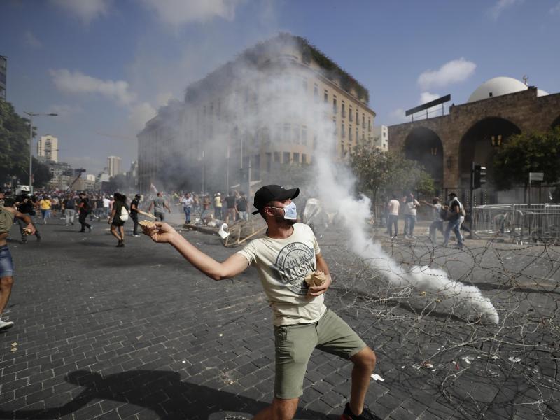 Ein Demonstrant wirft einen Stein auf Sicherheitskräfte. Foto: Hassan Ammar/AP/dpa