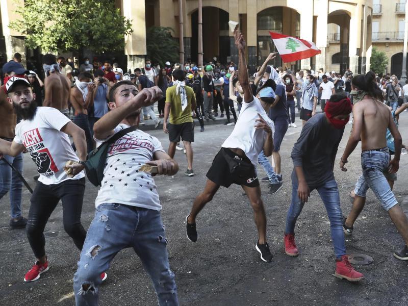Demonstranten werfen in Beirut Steine auf libanesische Bereitschaftspolizisten. Foto: Bilal Hussein/AP/dpa