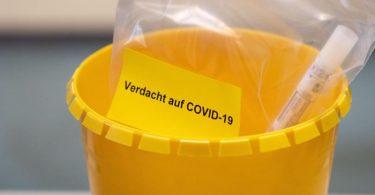 Ein Teströhrchen liegt in einer Tüte mit der Aufschrift «Verdacht auf COVID-19». Foto: Marius Becker/dpa