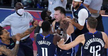 Luka Doncic (M) von den Dallas Mavericks feiert mit seinen Teamkollegen. Foto: Ashley Landis/Pool AP/dpa