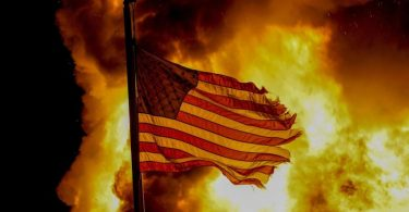 Eine US-Flagge weht vor einem Feuer, das bei Protesten vor dem Gebäude einer Strafvollzugsanstalt in Kenosha lodert. Foto: Morry Gash/AP/dpa