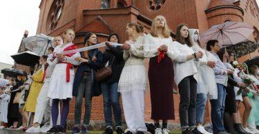 """Demonstrantinnen stehen während einer Kundgebung mit einem """"Warteband"""", einem Symbol des Protests, in Minsk. Foto: Dmitri Lovetsky/AP/dpa"""