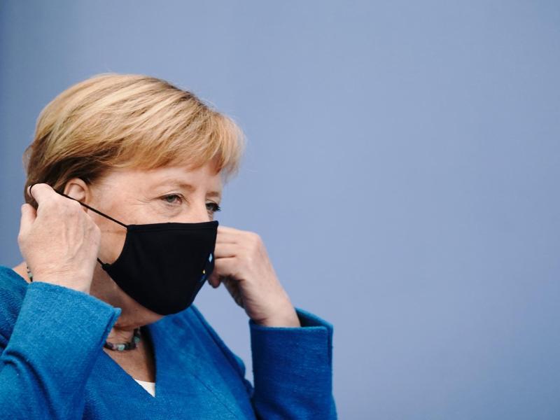 Bundeskanzlerin Angela Merkel nimmt vor ihrer traditionellen Sommer-Pressekonferenz zu aktuellen innen- und außenpolitischen Themen ihre Maske ab. Foto: Michael Kappeler/dpa-Pool/dpa