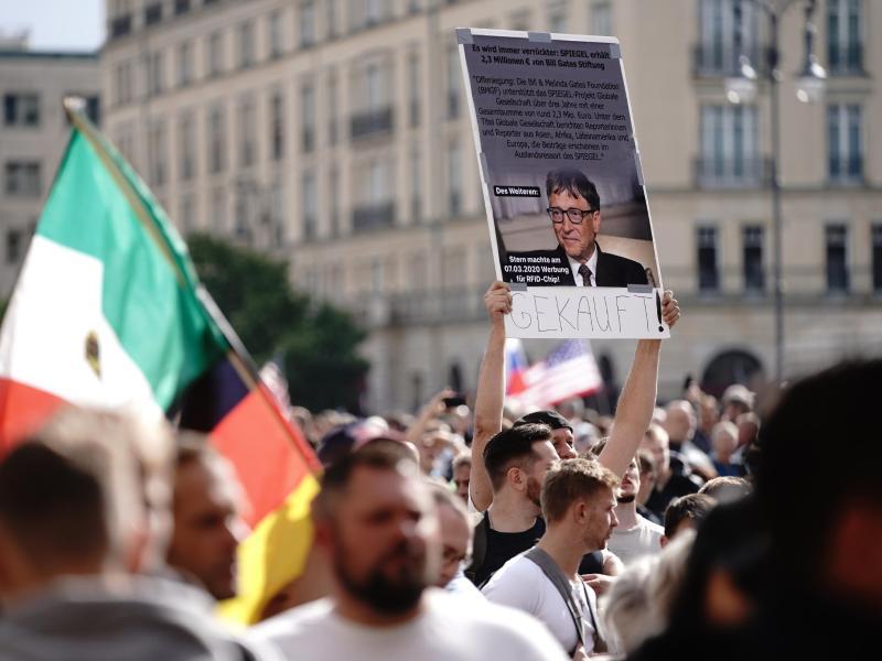 Ein Teilnehmer hält ein Plakat von Bill Gates und dem Schriftzug Gekauft! vor einer Demonstration gegen die Corona-Maßnahmen. Foto: Kay Nietfeld/dpa