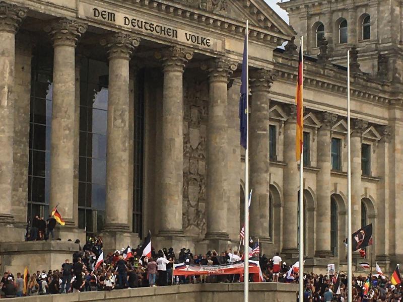 Teilnehmer einer Kundgebung gegen die Corona-Maßnahmen stehen vor dem Reichstag. Foto: Lukas Dubro/dpa