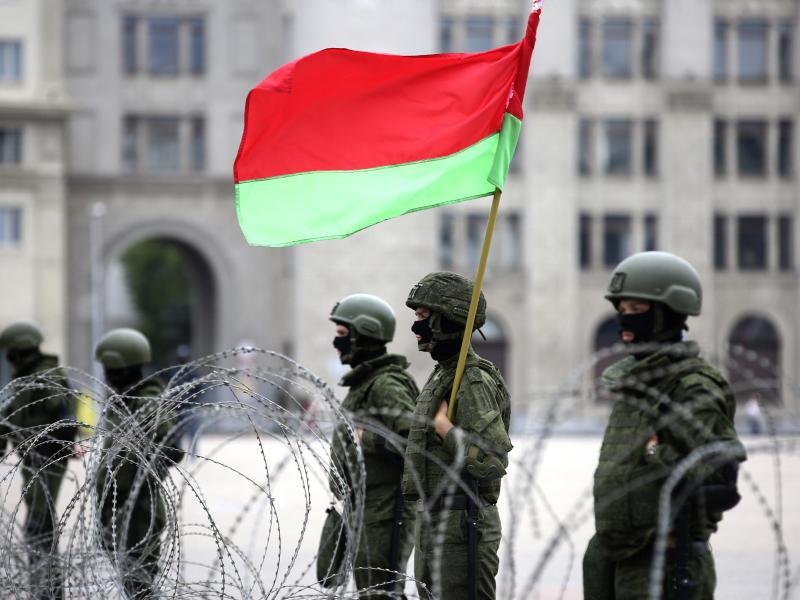 Uniformierte Sicherheitskräfte stehen in Minsk mit der belarussischen Staatsflagge hinter Stacheldraht. Foto: Uncredited/Tut.by/AP/dpa