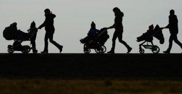 Drei Mütter schieben ihre Kinderwagen eine Landstraße entlang. Ab diesem Montag erhalten die Eltern von rund 18 Millionen Kindern in Deutschland 300 Euro extra. Foto: Felix Kästle/dpa
