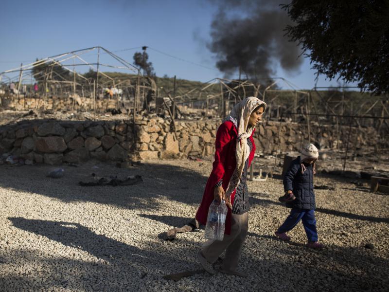 Eine Frau geht mit ihren Kindern durch das ausgebrannte Flüchtlingslager Moria. Foto: Socrates Baltagiannis/dpa