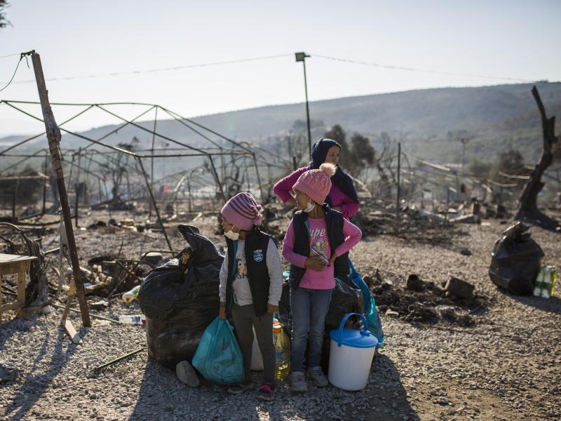 Eine Familie steht innerhalb des ausgebrannten Flüchtlingslagers Moria. Mehrere Brände haben das Lager fast vollständig zerstört. Foto: Socrates Baltagiannis/dpa