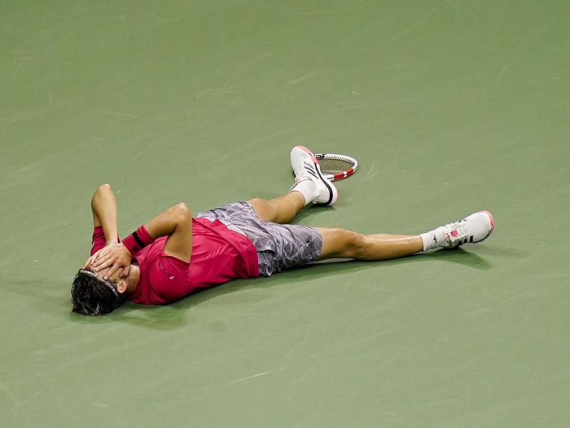 Nach seinem Sieg lässt sich Dominic Thiem rücklings auf den Boden fallen. Foto: Seth Wenig/AP/dpa