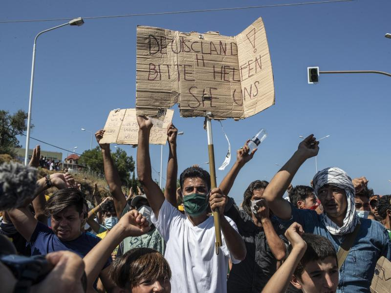 Ein Flüchtling auf Lesbos hält ein Plakat mit der Aufschrift «Deutschland, bitte helfen sie uns». Foto: Petros Giannakouris/AP/dpa