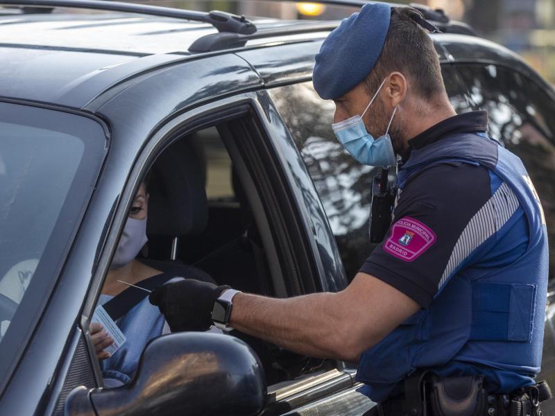 Ein Polizist spricht an einem Kontrollpunkt in Madrid mit einer Autofahrerin. Foto: Manu Fernandez/AP/dpa