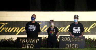 «Trump lied» - «200.000 died»: Demonstranten halten in der Nähe des Trump International Golf Club in Palm Beach eine Mahnwache ab. Foto: Meghan Mccarthy/Palm Beach Post via ZUMA Wire/dpa