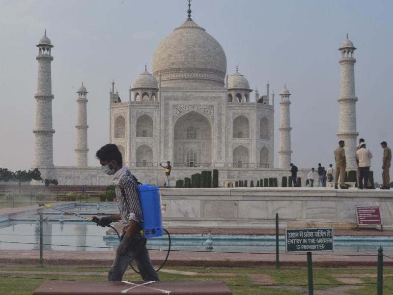Ein Mann sprüht Desinfektionsmittel in einem Bereich vor dem Taj Mahal im nordindischen Agra. Das berühmte Mausoleum ist für Besucher wiedereröffnet worden, nachdem es Corona-bedingt mehr als sechs Monate lang geschlossen war. Foto: Pawan Sharma/AP/dpa