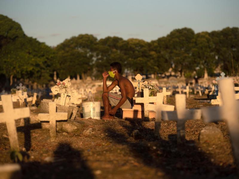 Ein junger Mann sitzt auf einem Friedhof in Rio de Janeiro, auf dem viele Opfer der Corona-Pandemie begraben worden sind. Foto: Fabio Teixeira/ZUMA Wire/dpa