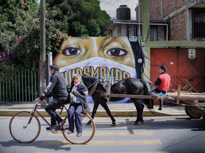 Radfahrer und ein Pferdekarren fahren im mexikanischen Tepetitla an einer Wandmalerei vorbei, die die Bevölkerung zum Maskentragen gegen eine Corona-Infektion auffordert. Foto: Jesus Alvarado/dpa