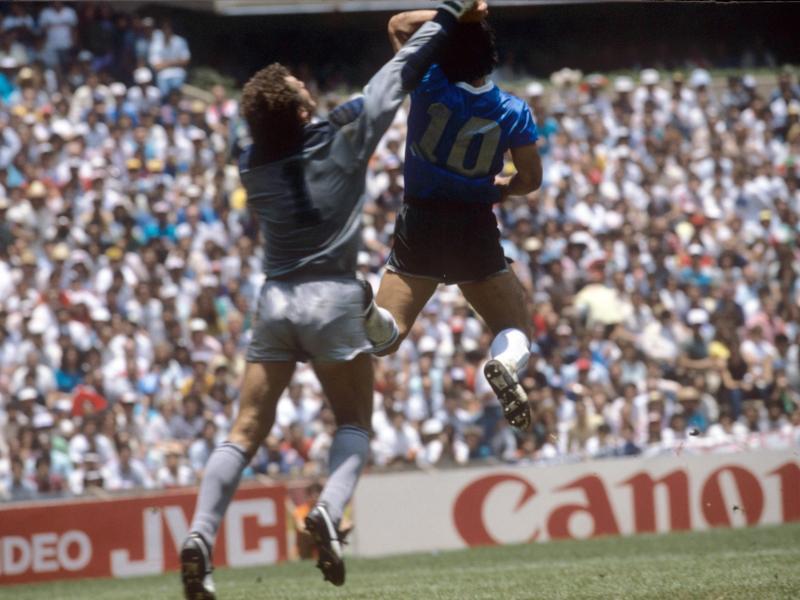 Die 'Hand Gottes': Maradona (r) erzielt bei der WM 1986 mit der Hand ein Tor gegen England und deren Schlussmann Peter Shilton. Foto: picture alliance / dpa