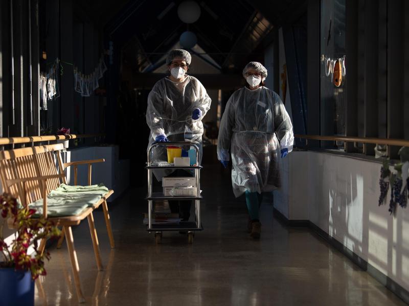 Zwei Altenpflegerinnen testen Altenheimbewohner auf Corona. Die Fallzahlen bleiben weiter auffallend hoch. Foto: Sebastian Gollnow/dpa