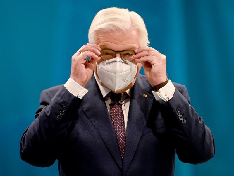 Bundespräsident Frank-Walter Steinmeier setzt sich einen Mund-Nasen-Schutz auf. Foto: Britta Pedersen/dpa/Archivbild