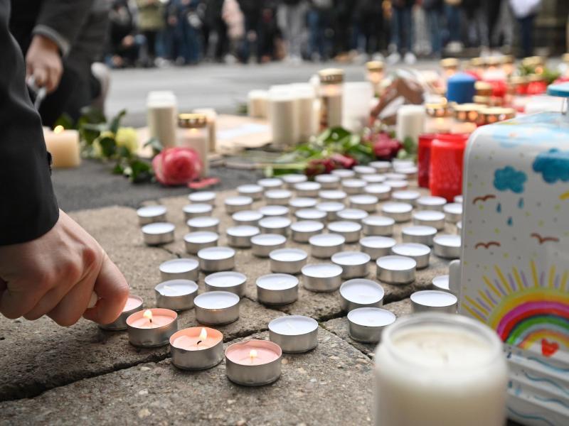 Trauernde zünden nach der Amokfahrt mit fünf Toten inTrier an der Porta Nigra Kerzen an. Zahlreiche Menschen gedenken hier der Opfer der Amokfahrt eines 51-jährigen Mannes durch die Innenstadt. Foto: Harald Tittel/dpa