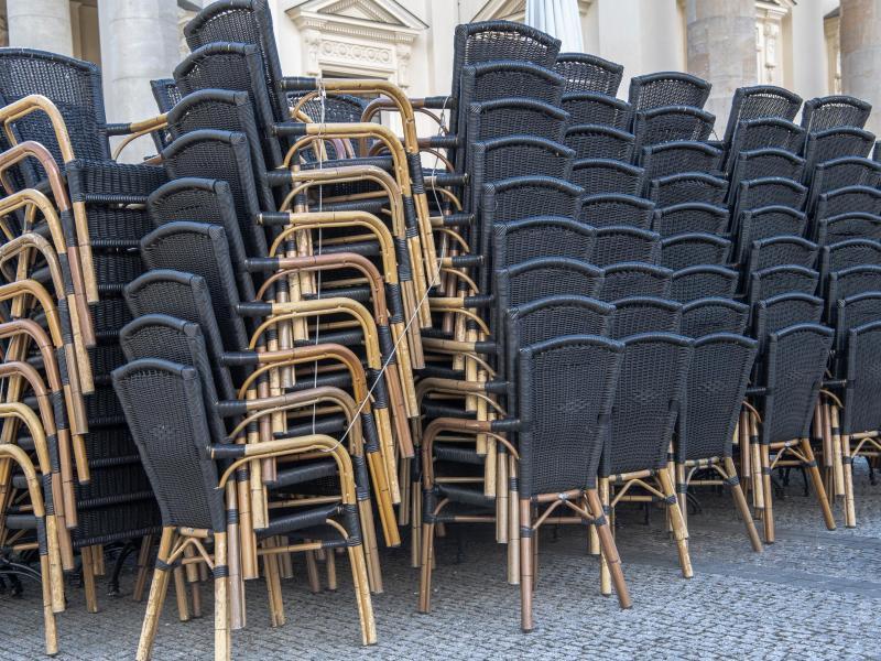 Zusammengestellte Stühle stehen vor einem gastronomischen Betrieb in Potsdam. Foto: Paul Zinken/dpa-Zentralbild/dpa