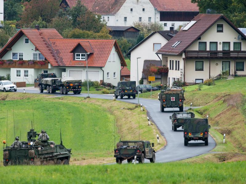 Militärfahrzeuge der US-Armee fahren durch den Ort Kleinfalz nahe dem Truppenübungsplatz Grafenwöhr inBayern. Foto: Armin Weigel/dpa/Archiv
