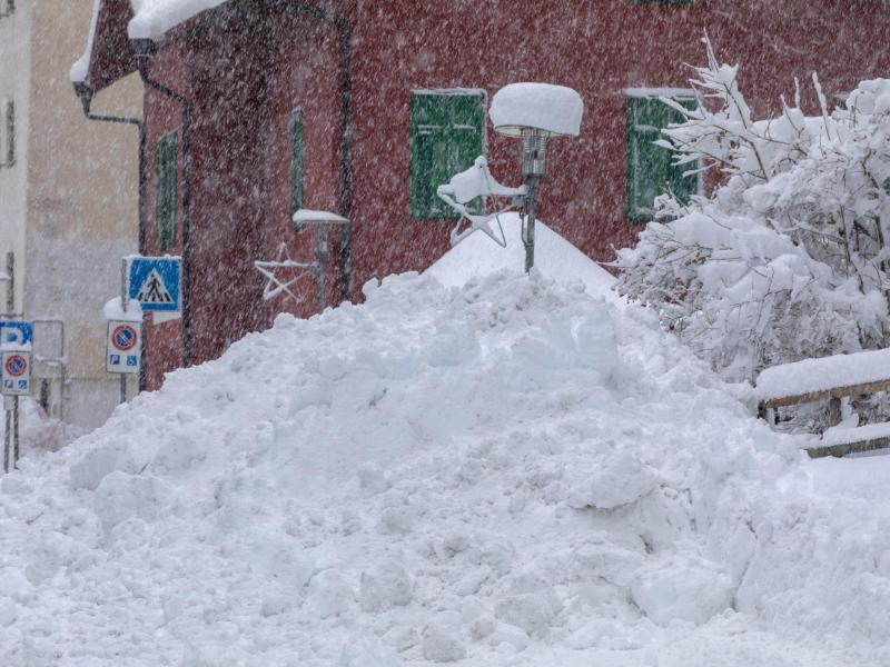 Schnee liegt hoch aufgetürmt am Straßenrand in der Gemeinde Brenner in Südtirol. Foto: Bernd März/dpa-Zentralbild/dpa