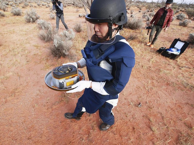 Ein Wissenschaftler hält in der Wüste des Woomera-Testgeländes für Luft- und Raumfahrt im Süden Australiens die Probenkapsel der japanischen Raumsonde 'Hayabusa2'. Foto: -/JAXA/AP/dpa