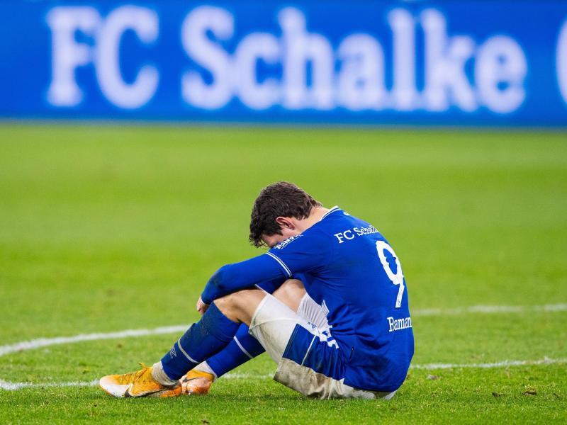 Schalkes Benito Raman sitzt nach dem Abpfiff auf dem Rasen. Foto: Guido Kirchner/dpa