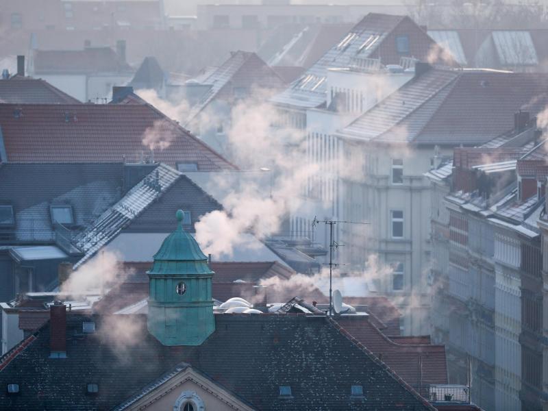 Rauch strömt aus den Kaminen auf den Dächern der Mehrfamilienhäuser im Leipziger Süden an einem kalten Wintermorgen. Foto: Jan Woitas/dpa-Zentralbild/dpa