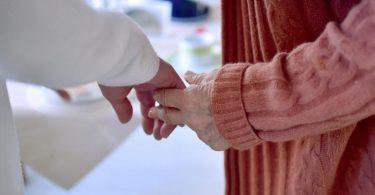 Eine Pflegekraft hält die Hand einer Bewohnerin einer Pflegeeinrichtung. Foto: Britta Pedersen/dpa-Zentralbild/Symbolbild/Archiv