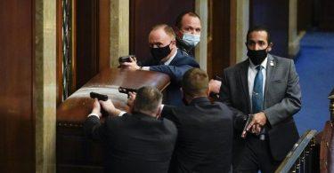 Sicherheitsleute des Kapitols stehen mit gezogenen Waffen hinter einer verbarrikadierten Tür. Foto: Andrew Harnik/AP/dpa