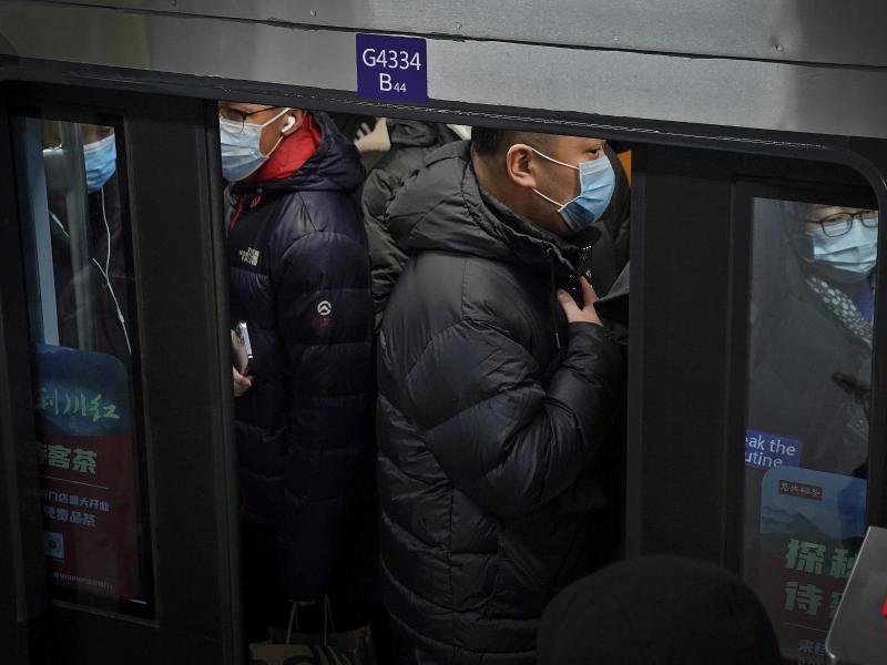 Pendler in Peking drängen sich während der Hauptverkehrszeit in eine U-Bahn. Foto: Andy Wong/AP/dpa