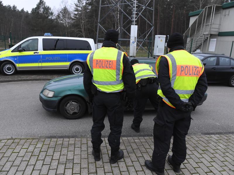 Polizisten kontrollieren ein Fahrzeug vor einem Grenzübergang nach Polen. Foto: Stefan Sauer/dpa