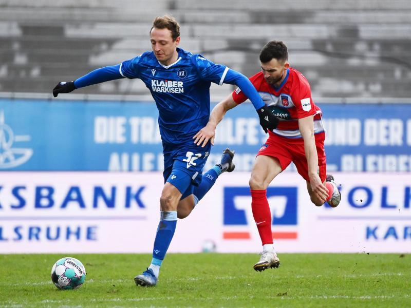 Karlsruhes Robin Bormuth (l) und Heidenheims Denis Thomalla teilten sich mit ihren Teams die Punkte. Foto: Uli Deck/dpa